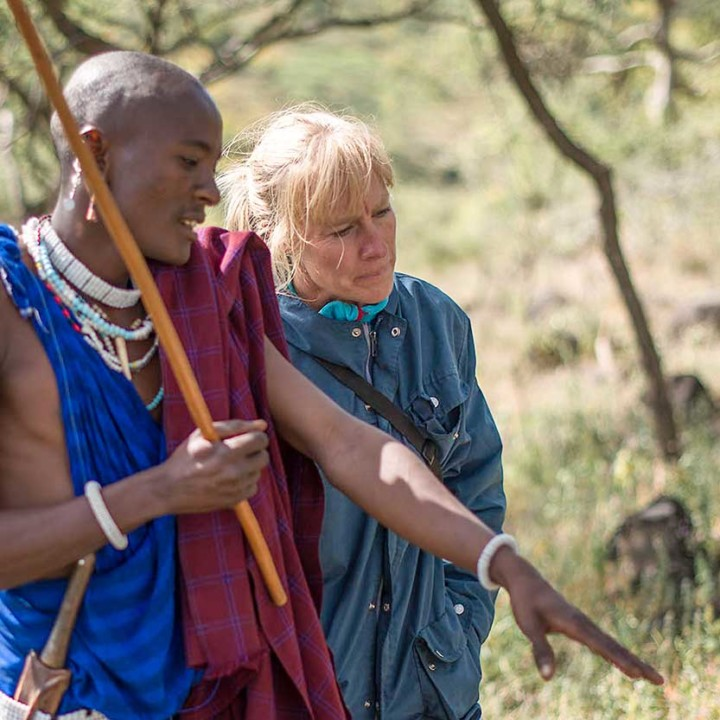 Lion Scout Kayanda pointing out recent tracks of lions to Ingela.