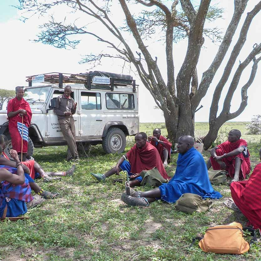 KopeLion staff gathering under a shady tree. Aloyce and William here explain the different, yet similar and complementary, roles of Ilchokuti and Lion Scouts.