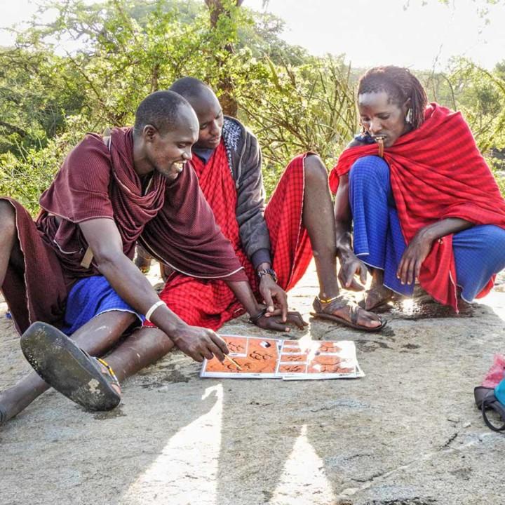 KopeLion ilchokutis (lion guardians) studying different lion tracks.